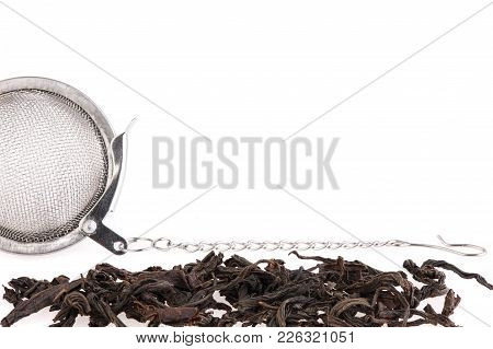 Black Tea, And Tea Strainer With Chain, Isolated On A White Background. A Black Tea And Tea Strainer