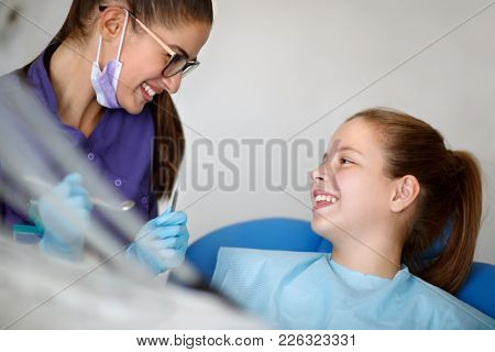 Smiling little patient with smiling female dentist starting checkup