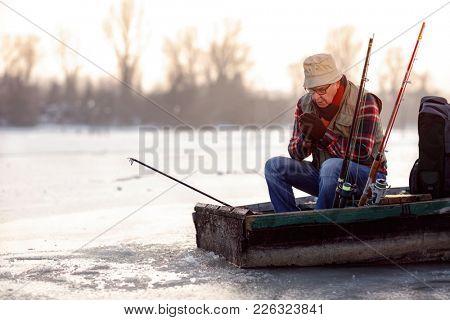 Winter season- elderly man fishing on the frozen river