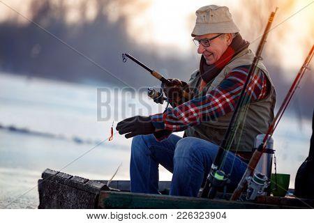 Winter hobby -elderly man fishing on lake