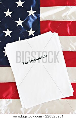 Tax Documents On A Usa Flag In A Pile.
