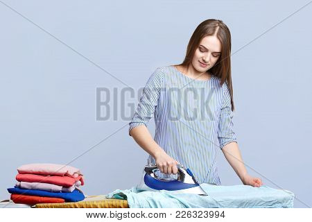 Beautiful Brunette Housewife Irons Clothes On Ironing Boards, Peals It Neatly, Being Busy All Day Lo