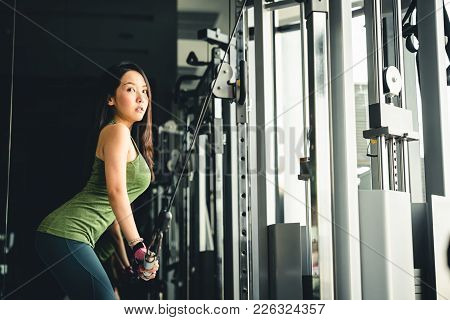 Sexy Young Asian Girl Exercising At Gym, Training On Pushdown Cable Machine, With Copy Space. Health