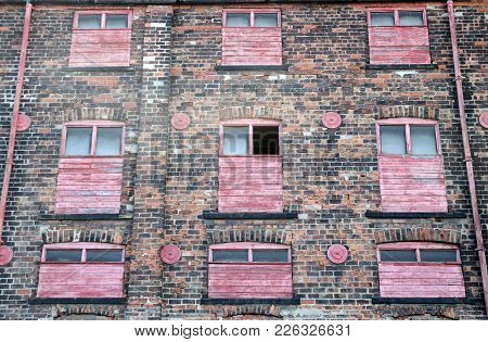 Facade Of A Derelict Abandoned Old Brick Industrial Building With Red Painted Broken Boarded Up Deca