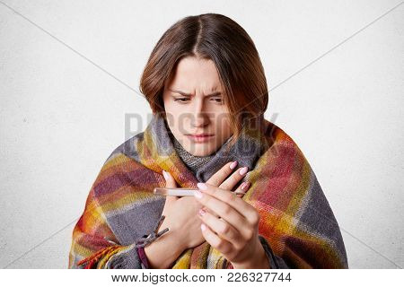 Displeased Ill Woman Wrapped In Plaid Looks At Thermometer, Has High Temperature And Cold, Caught Ch