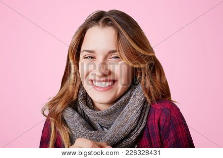 Adorble Smiling Young Female Wears Scarf On Neck, Dressed In Checkered Shirt, Has Pleasant Appearanc