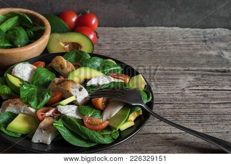 Salad With Avocado, Chicken, Spinach And Tomatoes Cherry In Black Plate With Fork. High Protein Food