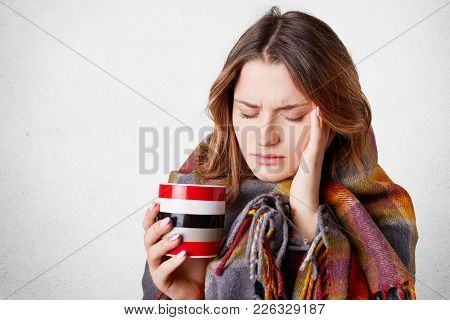 Frustrated Ill Young Woman Covered In Warm Blanket, Keeps Hand On Temple, Suffers From Terrible Head