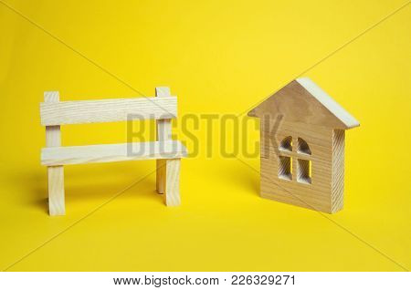 Wooden House And Bench On A Yellow Background. The Concept Of The Real Estate Market. Prices Demand