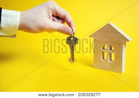The Hand Holds The Keys On The Background Of The House. Wooden House On A Yellow Background. Buying