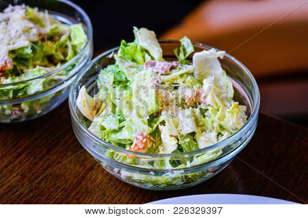 Caesar Salad In A Glass Bowl Placed On Table. Lettuce Dressed With Parmesan Cheese, Lemon Juice, Oli
