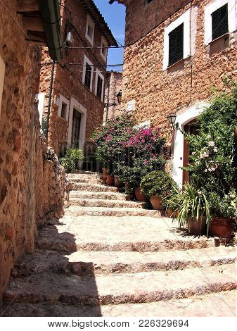 Narrow Cobble Stone Street With Plants In Fornalutx, Spain