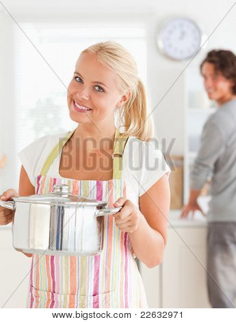 Portrait of a woman posing while her fiance is washing the dishes in their kitchen
