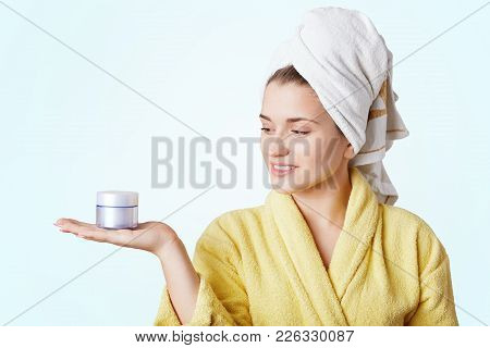 Portrait Of Beautiful Young Woman Wears Bathrobe And Towel, Holds Cream, Going To Make Face Mask, Is