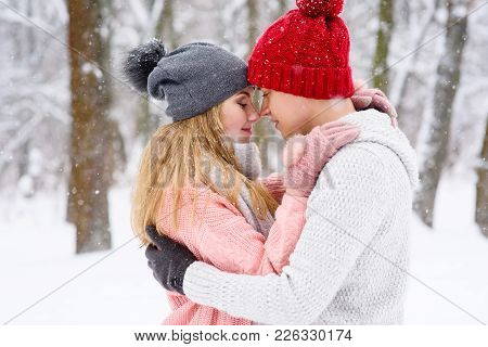 Portrait Of Gilr And Boy Holding Each Other In Knitted Sweaters And Hats During Snowfall