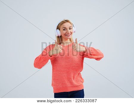 positive blond in headphones showing thumbs up