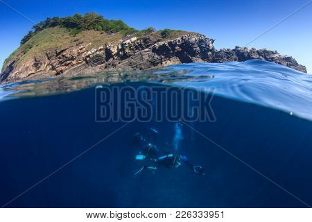 Scuba diving beside tropical island. Half and half over under split photo