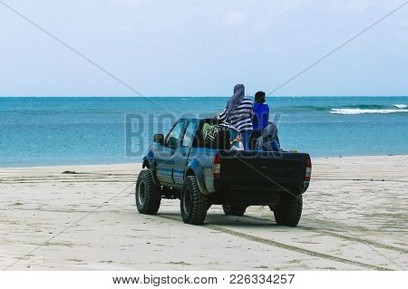Kudat,sabah-feb 3,2018:a Black Four Wheel Vehicle With Kids Enjoying Driving Along The Sandy Tropica