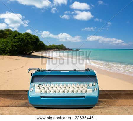 Modern Electric Typewriter On Wooden Desk With Ocean Beach Background Suggesting Deserted Island
