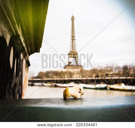 Bitten Apple Core Left On Paris Bridge With Eiffel Tower In The Background Sunlight Flare