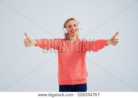 funny blond in headphones showing thumbs up