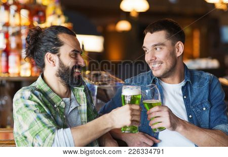leisure, friendship, st patricks day and celebration concept - happy male friends drinking green beer and clinking glasses at bar or pub