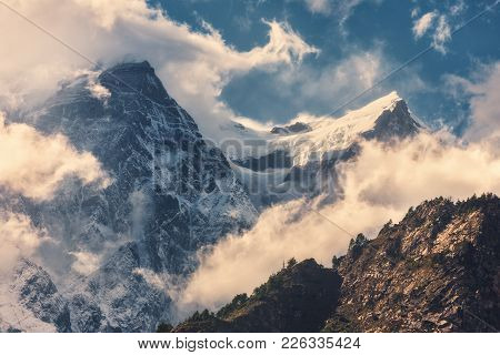 Mountains With Snowy Peaks In Clouds At Sunset