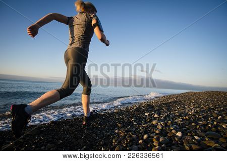 Adult Woman Runner Running On Sunrise Seaside. Healthy Lifestyle.