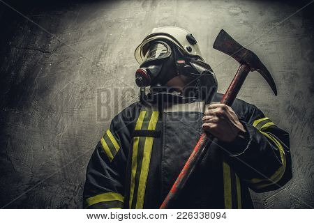 Portrait Of Firefighter In Oxygen Mask Holding Red Rescue Axe.