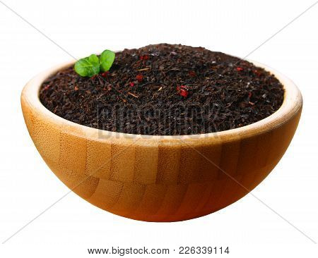 Black Dry Tea In A Wooden Bowl Isolated On White Background