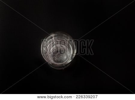 A Glass Of Water On A Black Background, A Place For The Text. Top View.