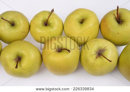 Two Rows Of Fresh Juicy Green Apples With Short Brown Cuttings, Top View, Close Up On A White Backgr