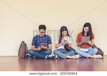 Group Of Asian College Student Using Tablet And Mobile Phone Outside Classroom. Happiness And Educat