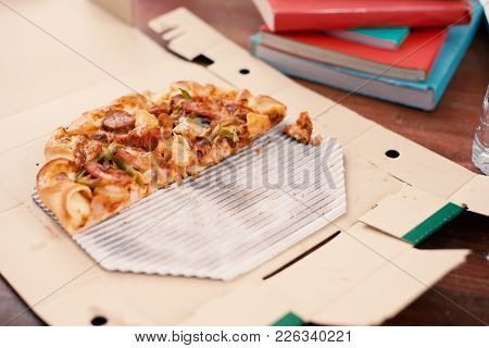 Piece Of Pizza On Table. Pizza On Table With Books And Drinks For Students Who Celebrating Party Aft