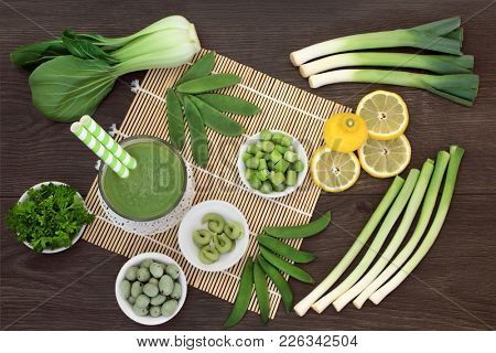 Japanese macrobiotic diet food detox concept with fresh vegetables, fruit, wasabi paste and nuts and cold matcha tea with foods high in antioxidants, fibre, vitamins and minerals. On bamboo and oak.
