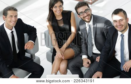 portrait of a smiling business team sitting in office lobby