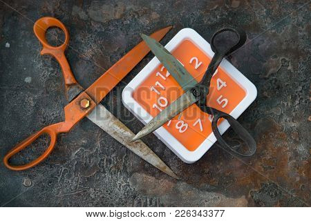 Orange Metal Scissors And Gray Scissors With Black Handles, Facing Each Other And A Square Clock Wit