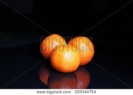 Mandarins On Black Reflective Studio Background. Isolated Black Shiny Mirror Mirrored Background For