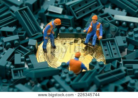 Miniature People Construction Worker Digs A Gold Bit Coin In The Middle Of A Green Jug Block. Commun