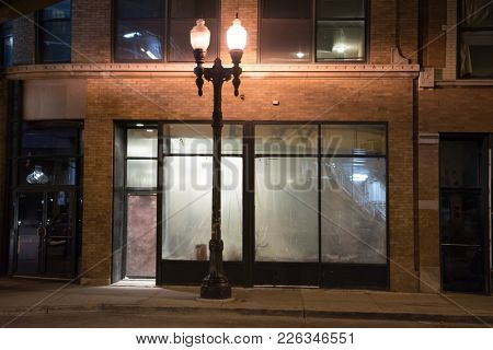Empty abandoned urban city storefront and vintage street lamp at night.