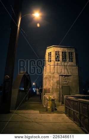 Vintage industrial city bridge with tower house and urban sidewalk at night.