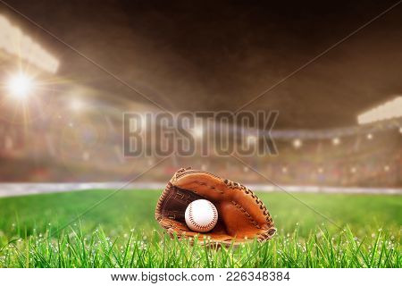 Baseball Glove And Ball On Grass In Brightly Lit Outdoor Stadium With Focus On Foreground And Shallo