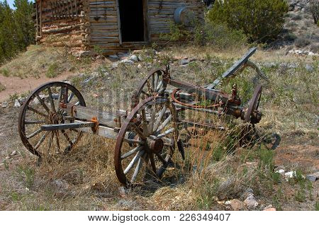 Old Wagon Sits In Front Of A Rustic, Log Cabin.  Steel Wheels And Wooden Frame Are All That Remain O