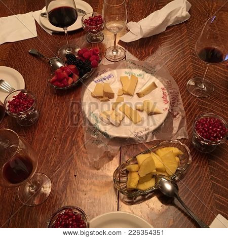 Appetizing Assortment Of Flavorful Fresh Cut Up Fruit And Gourmet Cheeses Plate, Wineglasses With Re