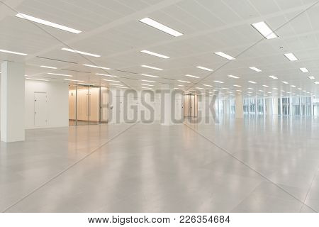 Huge Empty Office Building Interior With Illuminated Ceiling Lights
