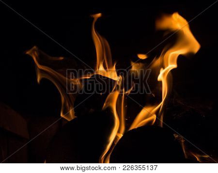 Burning Wood And Flames In A Fireplace On A Black Background