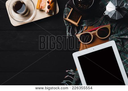 Wooden Black Table With Tablet,glasses,notebook And Cup Of Coffee.top View With Copyspace.