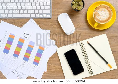Office Desk Table With Keyboard,pencil,mouse,smart Phone,financial Data Or Chat Or Graph And Cup Of