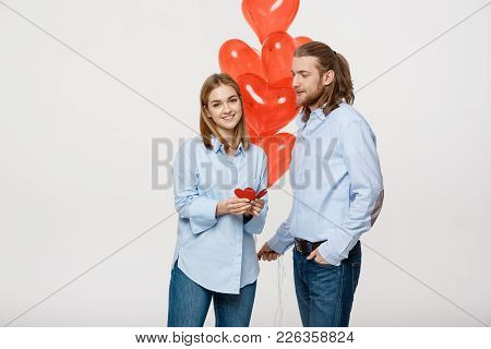 Young Attactive Caucasian Couple Holding Heart Balloon And Paper