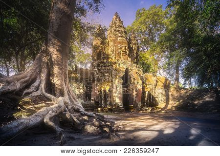 Ancient Gates Of Bayon Temple In Angkor Complex With Stone Faces Of Buddha And Jungle Around It Siem